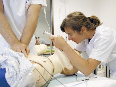 un soignant s'exerce sur un manequin